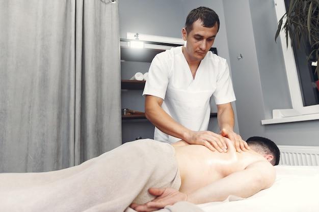 医者は病院で男をマッサージします