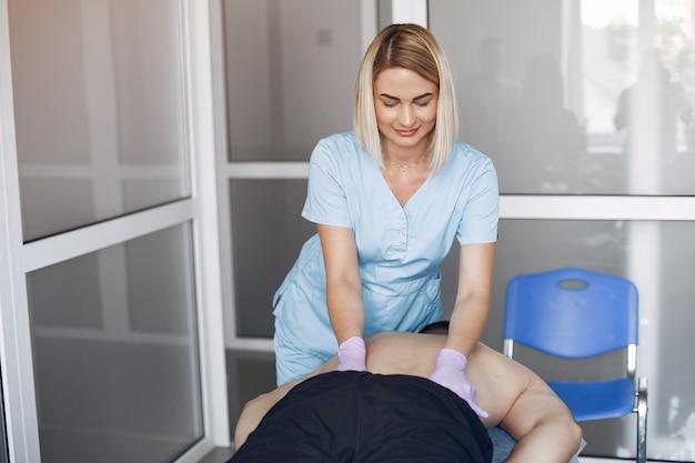 의사가 병원에서 남자를 마사지합니다.