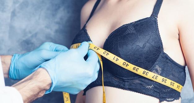 의사는 브래지어를 입은 여성의 가슴을 측정합니다.