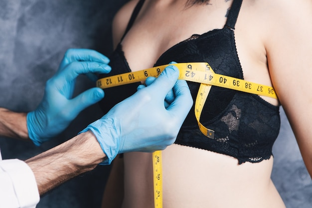 医者はテープで胸を測定します