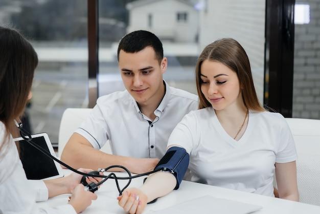 医師はクリニックで妊婦の圧力を測定します。妊娠と健康管理