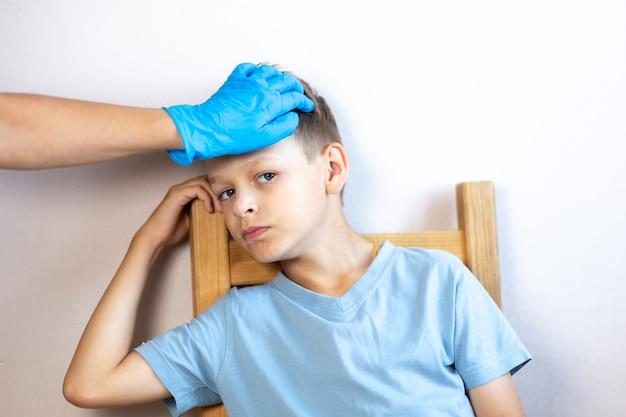 의사는 장갑을 낀 손으로 아픈 소년의 온도를 측정합니다 프리미엄 사진