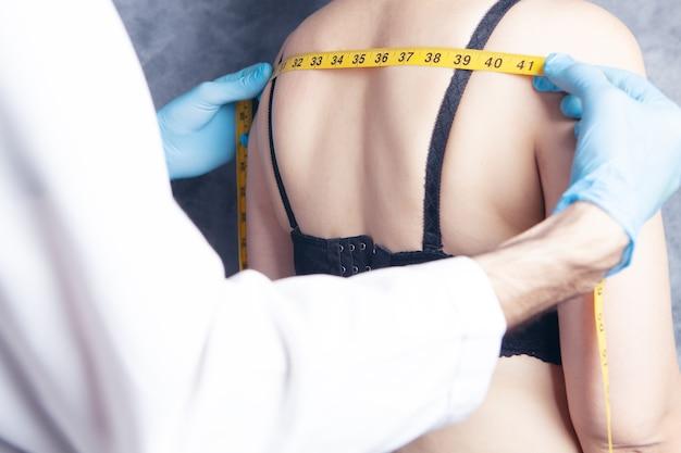 의사가 여성의 등을 측정합니다.