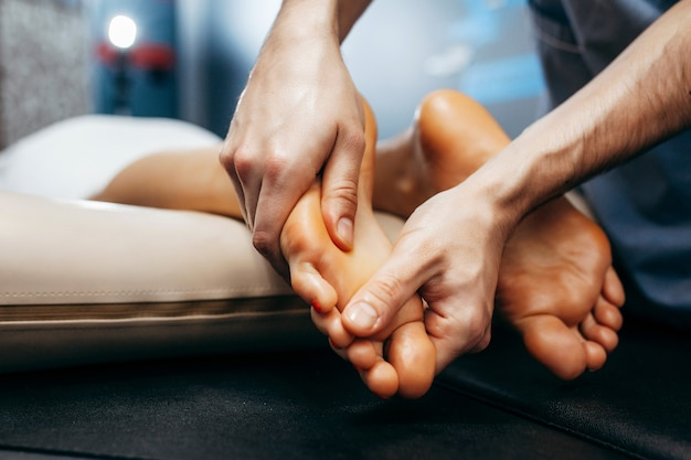 В клинике врач-ортопед проводит осмотр и массаж стопы пациента.