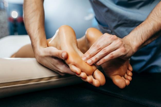 医師-足病医は、クリニックで患者の足の検査とマッサージを行います。