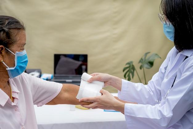 医者は事故を起こした年配の女性の腕に傷を負っている。