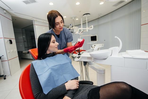 Врач показывает слепок челюсти пациента. лечение зубов