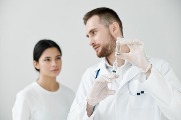 의사는 환자에게 백신과 보호 장갑이 달린 주사기를 보여줍니다.