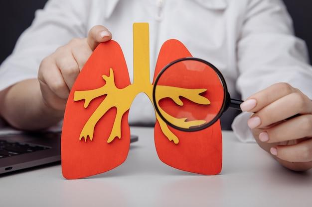 医者は肺の虫眼鏡を通して見せます。