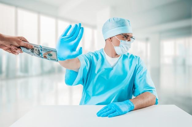 의사는 책상에 앉아 백 달러 지폐 묶음을 거부합니다.