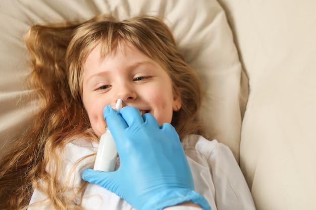 医者は女の子の鼻に点鼻薬をスプレーします