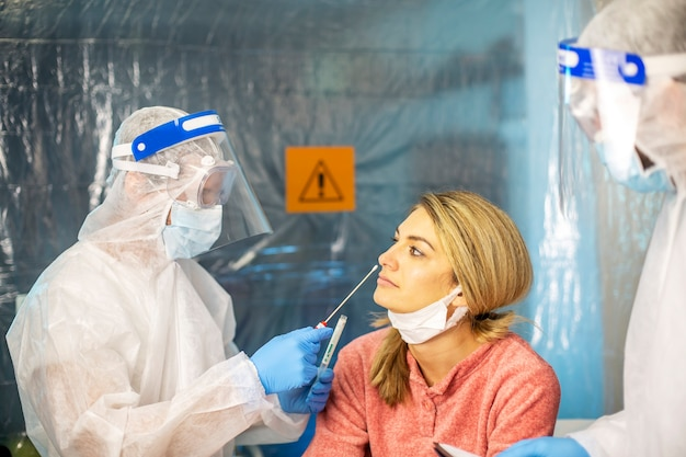 医者は病気の患者を綿棒で拭きます。ウイルスエピデミック