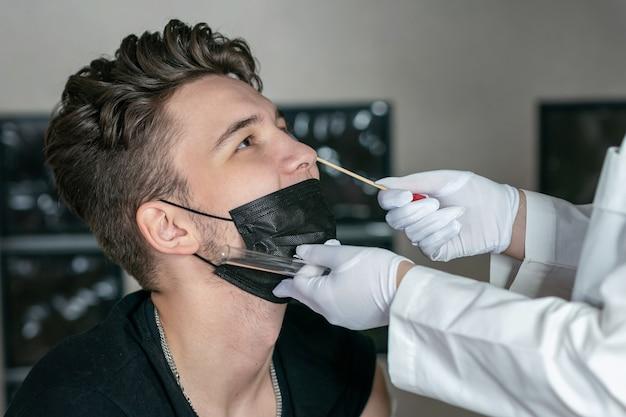 의사는 젊은 남자의 코 dna 테스트에서 면봉을 가져갑니다. pcr 테스트 선택적 초점