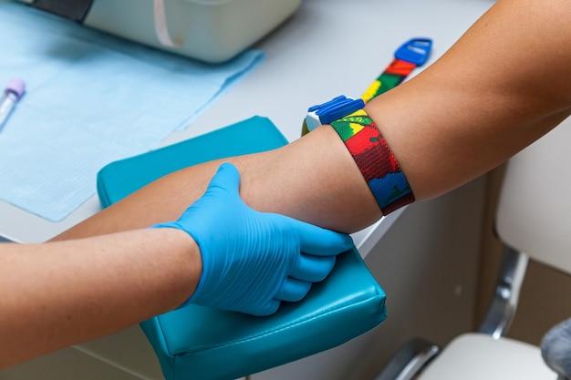医者は腕の静脈から血液を採取します