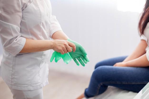 医者は手袋をはめています