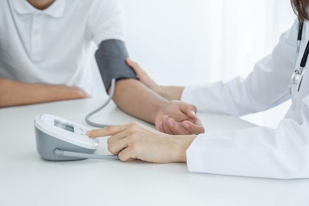 의사 여자 손은 환자의 압력, 건강 검진 개념을 측정하기 위해 맥박계를 사용합니다.