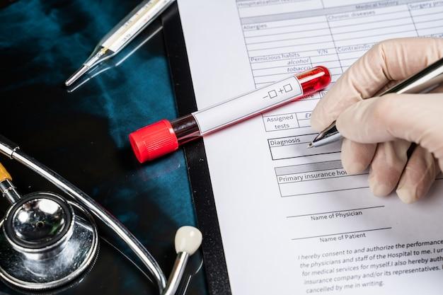 의사는 환자 양식에 진단을 씁니다. 의사가 폐 엑스레이로 질병 또는 대사 장애에 대한 혈액 검사를보고 있습니다.
