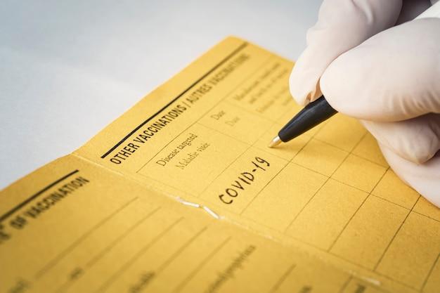 Врач пишет словом covid-19 название болезни, от которой проводится вакцинация. , международный, сертификат, вакцинация, вакцина,
