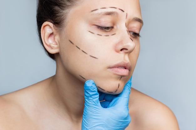 의사들은 장갑을 낀 손으로 피부에 자국을 보여주는 환자의 얼굴을 안고 있다. 안면 성형 수술
