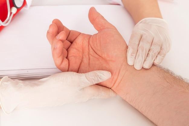 의사의 손이 환자 팔의 맥박을 측정합니다.