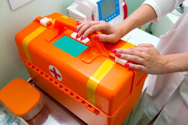 医師は最初の救急医療のオレンジ色のスーツケースを手渡します