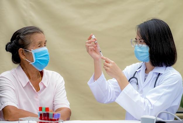 注射器を持っていて、クリニックで年配の患者の女性に予防接種をしようとしていた医師