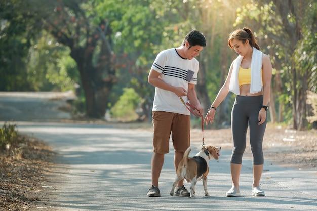 개와 주인은 공원에서 하루를 보냈습니다. 젊은 부부와 재미를 위해 달리는 개 여름 배경