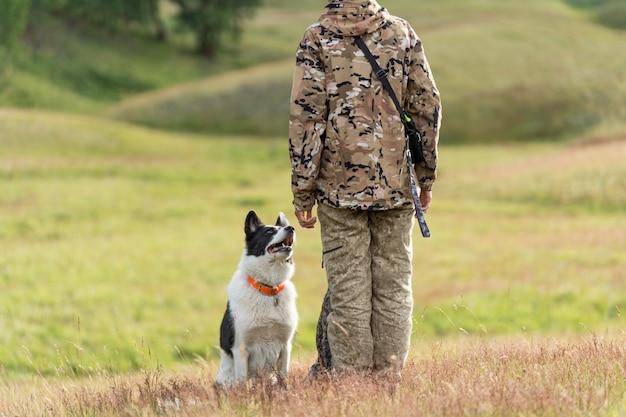 Собака выполняет команды своего хозяина. девушка-охотник тренирует свою собаку