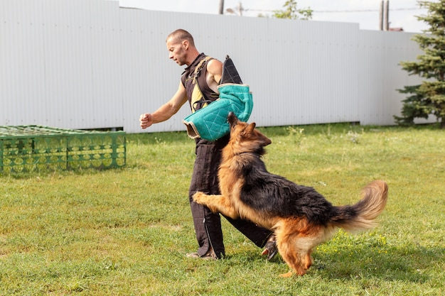 개 강사는 독일 셰퍼드 개와 함께 수업을 진행합니다. 개는 주인을 보호합니다.
