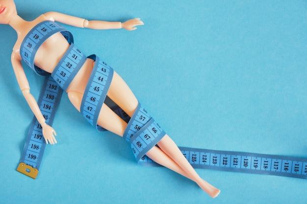 人形は巻尺、スリムさと食欲不振のカルトの概念、食事療法と体重減少で包まれています