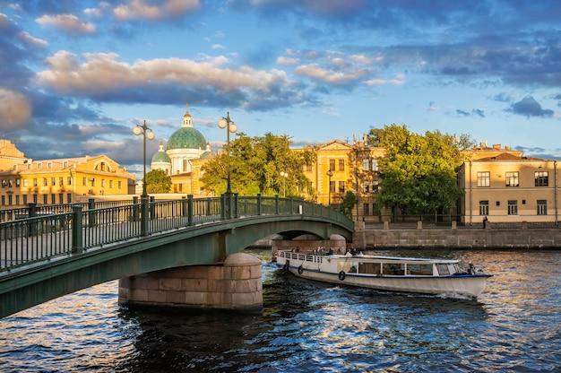 Купол измайловского собора и прогулочный корабль плывет под красноармейским мостом через реку фонтанку в санкт-петербурге летним солнечным вечером.