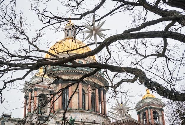 Купол исаакиевского собора в санкт-петербурге сквозь ветки деревьев и елочные игрушки в виде звезд под зимним небом