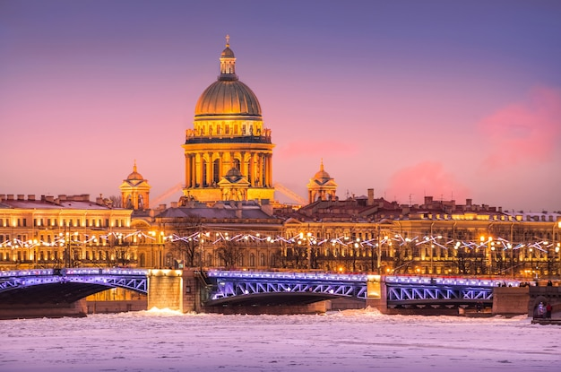 Купол исаакиевского собора, дворцовый мост и река нева во льду в санкт-петербурге в зимнюю сиреневую ночь
