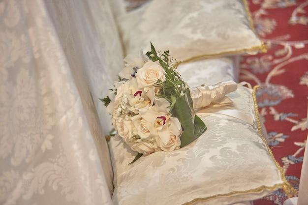教会内の結婚式のベンチの白いクッションの上に置かれたダブルブーケ