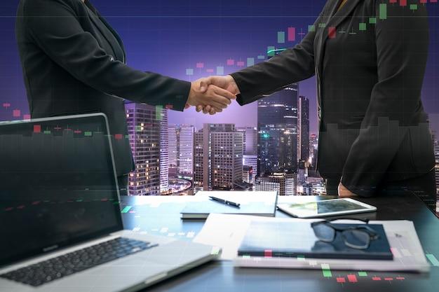 投資取引を成功させるためのビジネスハンドシェイクの二重露光画像