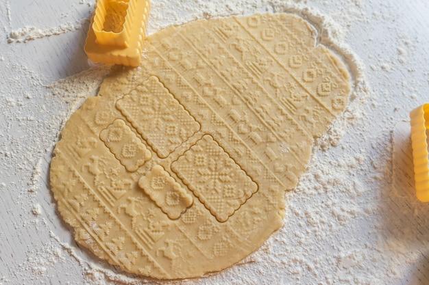 На столе раскатывается тесто с новогодним узором, рядом формочки для печенья.