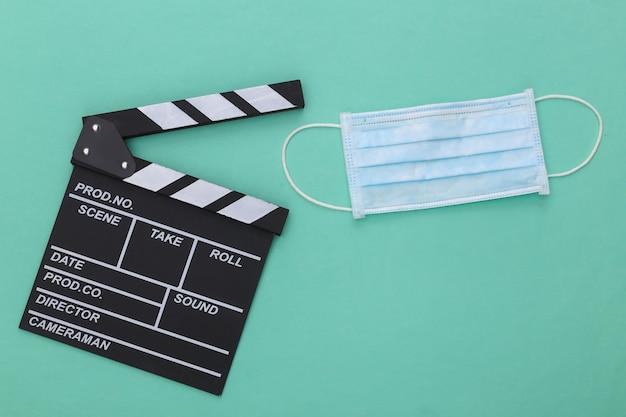 Спад в индустрии развлечений во время covid-19. доска с хлопушкой кино с медицинской маской на цветном фоне мяты. кинопроизводство. вид сверху
