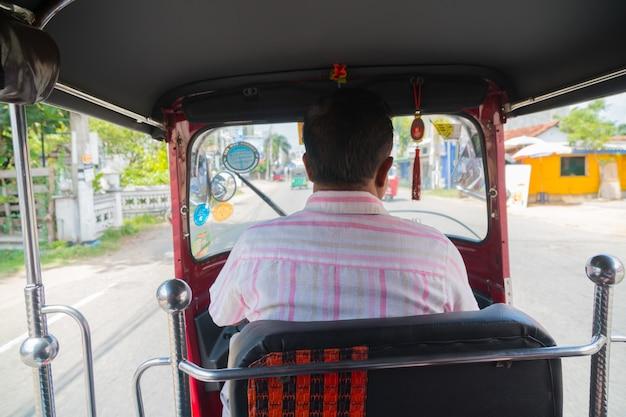 운전자는 그의 차 바퀴에서 뚱뚱한 두드리는 사람입니다.