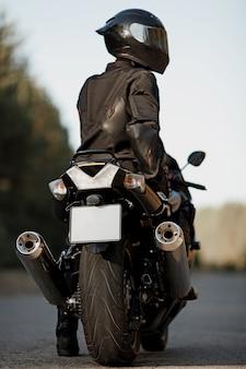 Водитель спортивного быстрого мотоцикла в шлеме повернулся спиной и смотрит вдаль.