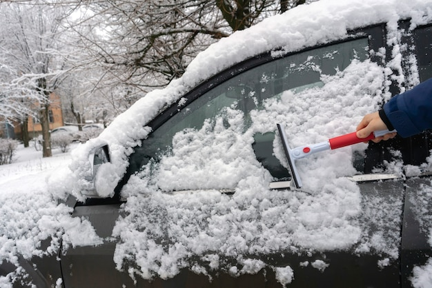 Рука водителя чистит машину от снега утром перед поездкой