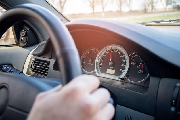 ドライバーがスピードアップします。車のインテリア。自動ルールの違反。ホイールに手を