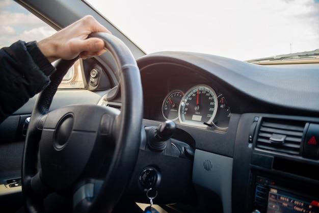 Штурвал с рукой водителя в современном салоне автомобиля с видом на улицу    Премиум Фото