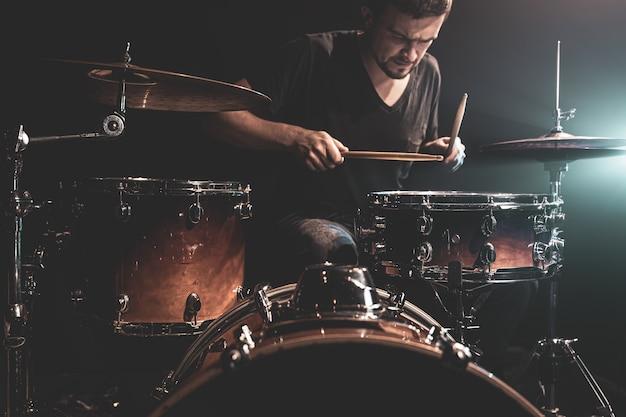 ドラマーはステージのドラムキットに座ってドラムを演奏します。