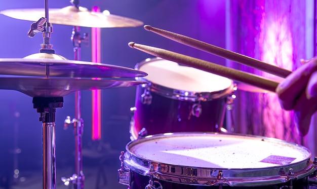 ドラマーは、美しい背景をクローズアップしてスタジオでドラムキットを演奏します。
