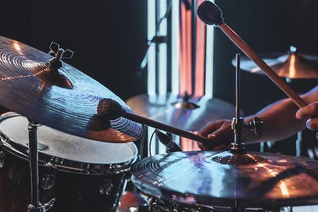 드러머는 흐릿한 배경에서 아름다운 조명으로 연주합니다.