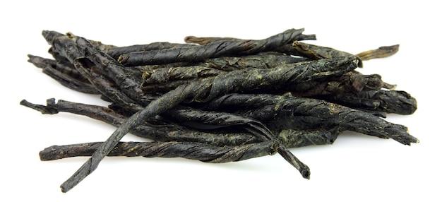 Сухие и плетеные листья зеленого чая на белом фоне