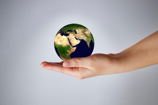 灰色の女性の手で地球