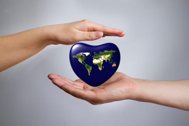 Земля в форме сердца в женских и мужских руках. 3d визуализация