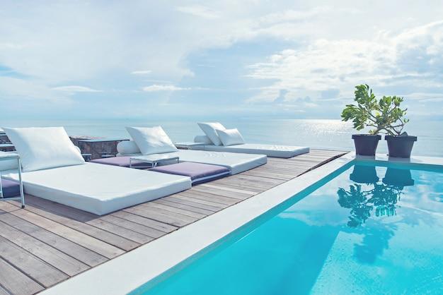 Роскошный бассейн с белыми модными шезлонгами на пляже.