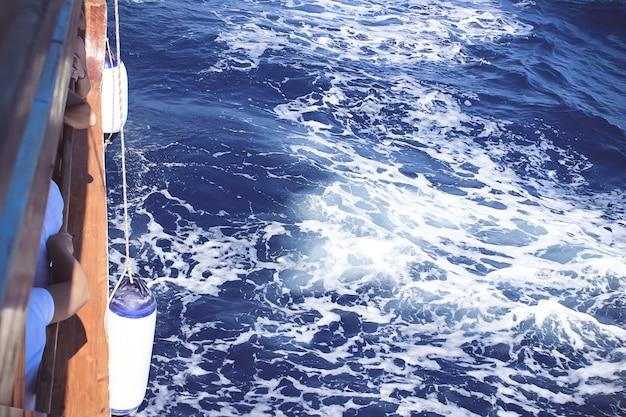 背景として海の泡と青い海水のヨットの端。スプレーで紺碧の海水。海の水の背景。